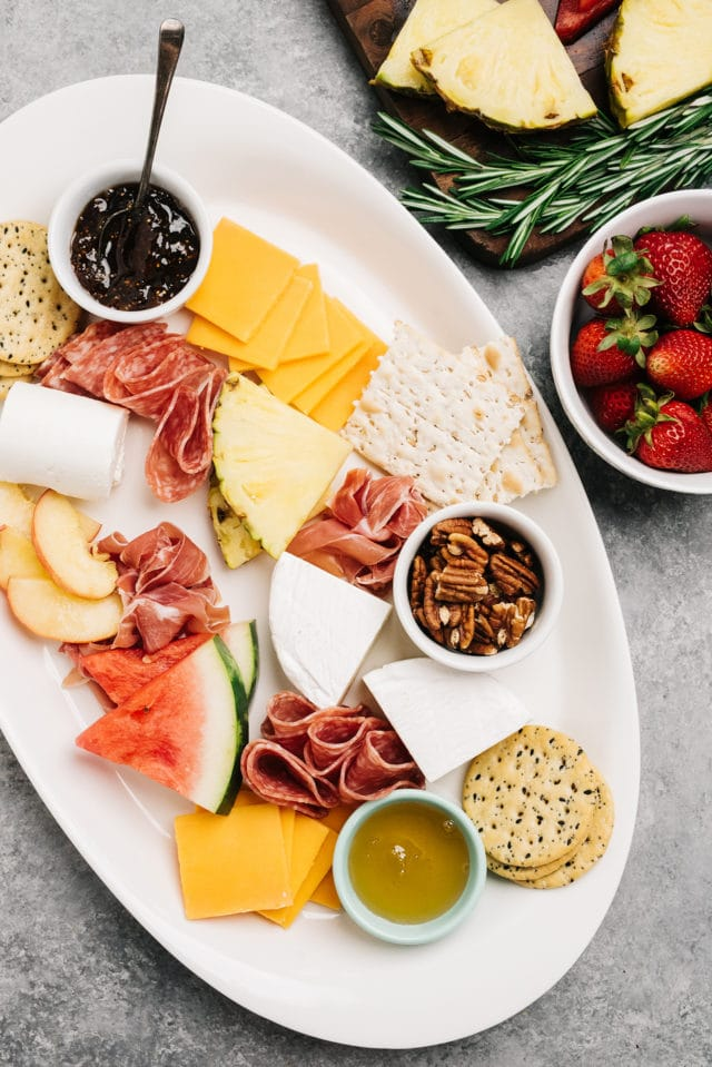 placing all of the ingredients on a serving platter for a summer charcuterie board