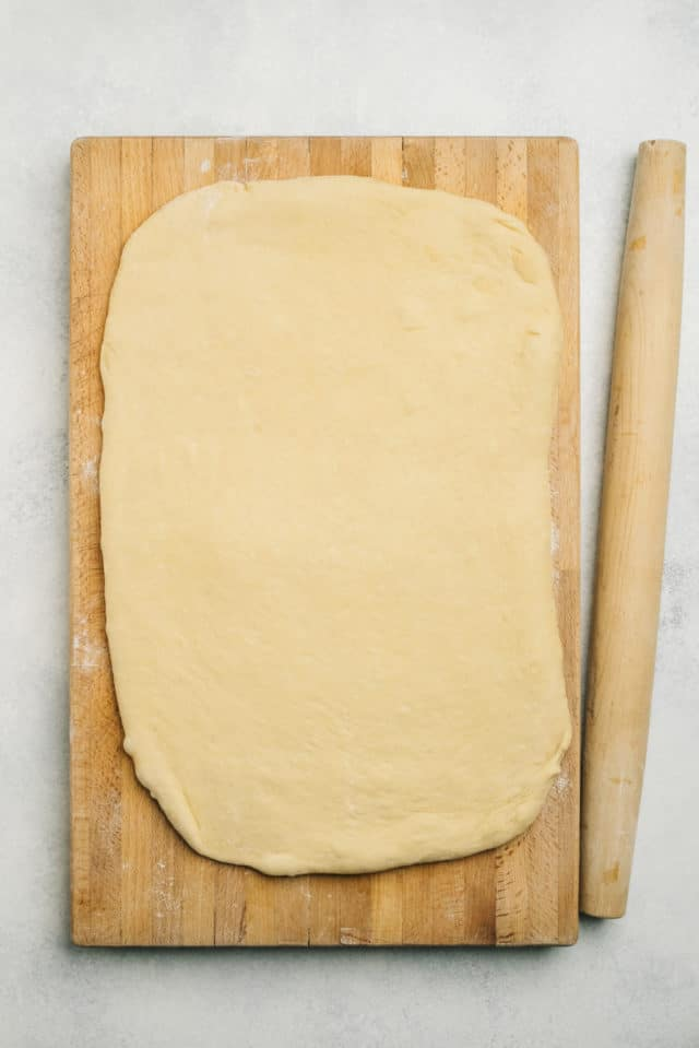 dough spread out in a rectangle shape on a wooden cutting board