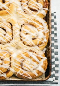 homemade cinnamon rolls with icing on a large baking sheet