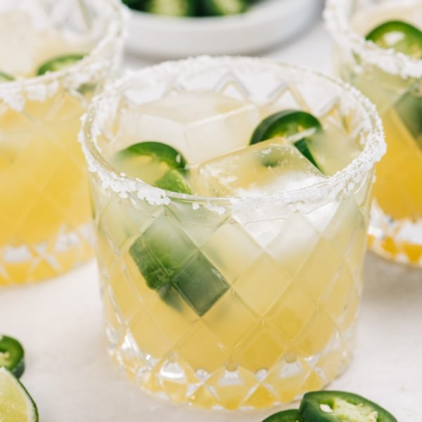 jalapeño margarita in a glass with salt on the rim and jalapeño slices
