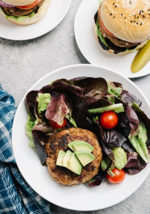 turkey burgers served in a salad with avocado and tomatoes