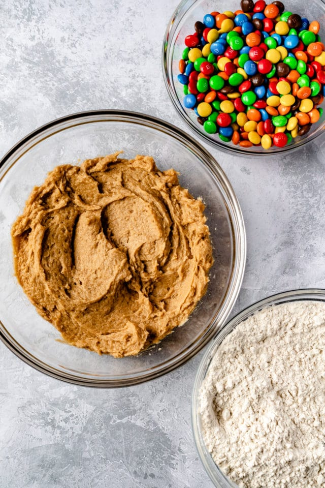 ingredients for M&M cookies in glass mixing bowls
