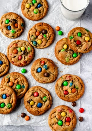 M&M Cookies spread out on parchment paper
