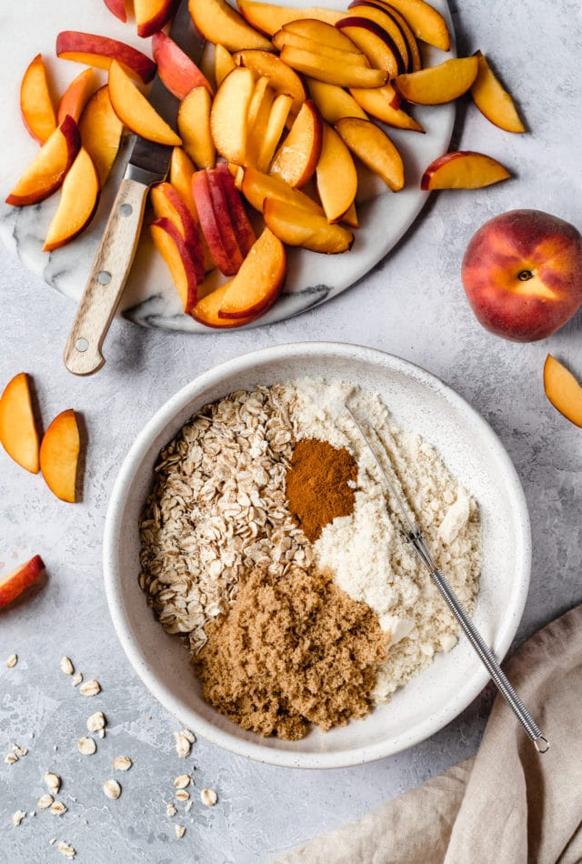 peaches sliced and ingredients for peach crisp topping in large white mixing bowl