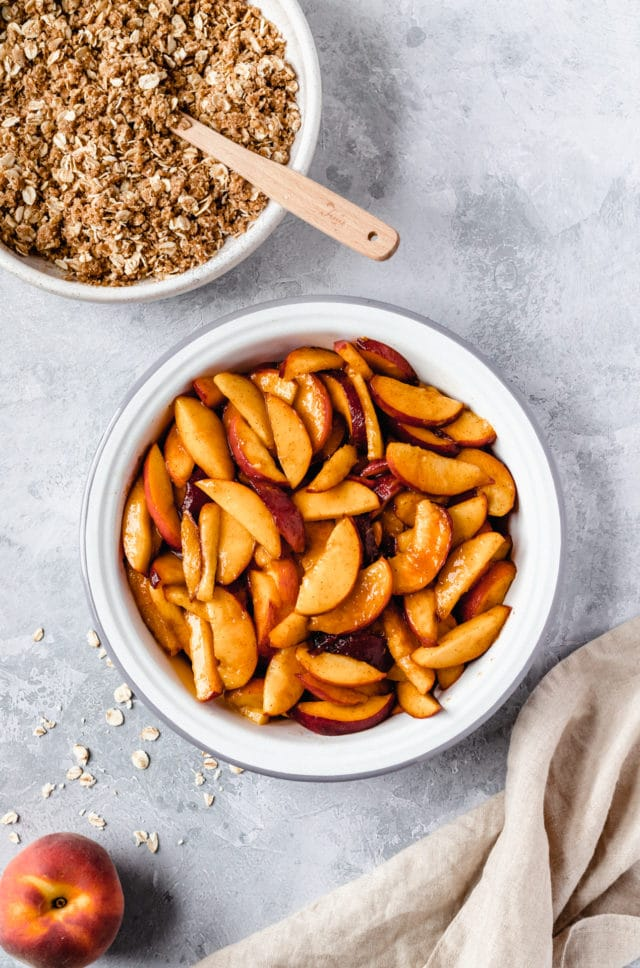 sliced peaches in a pie plate with a bowl of oat topping on the side