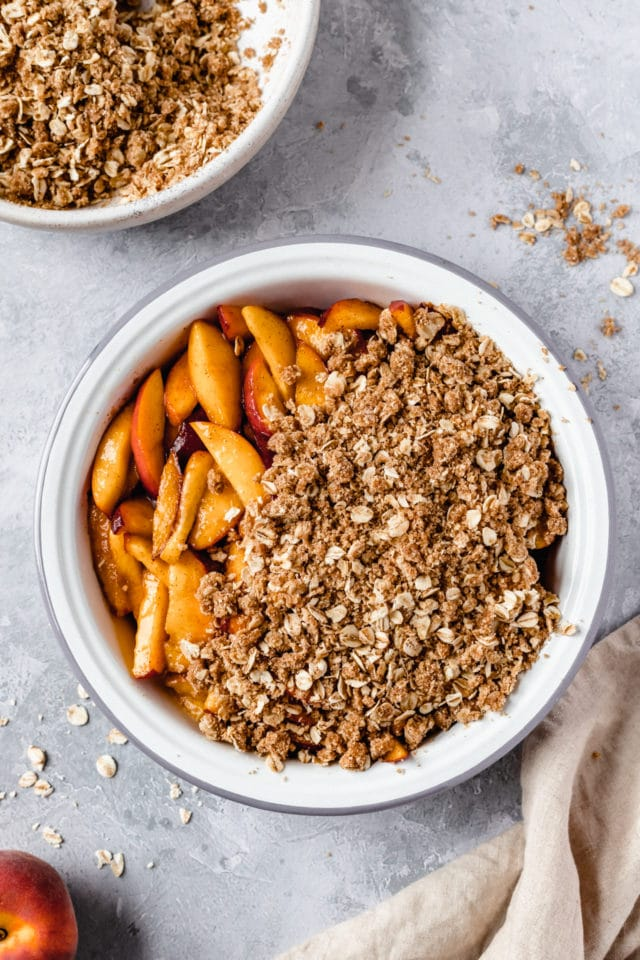 covering sliced peaches with oat topping for peach crisp