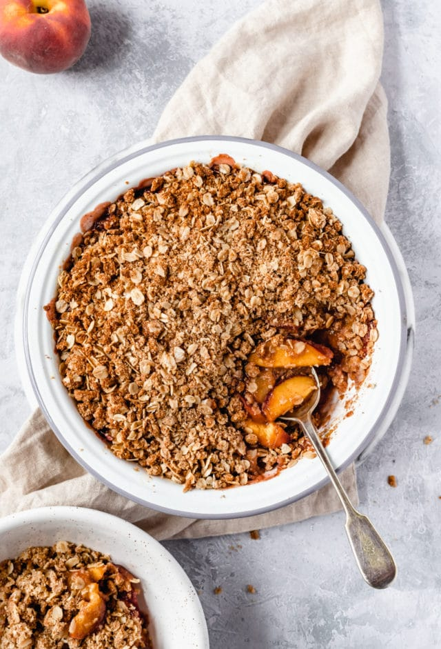 peach crisp in a white pie plate with a serving spoon