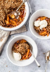 peach crisp served in small white bowls with vanilla ice cream