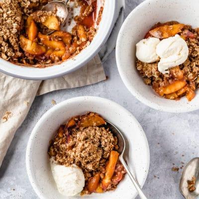 peach crisp served in small white bowls with vanilla ice cream