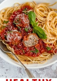Italian meatballs served with marinara and spaghetti in a white bowl
