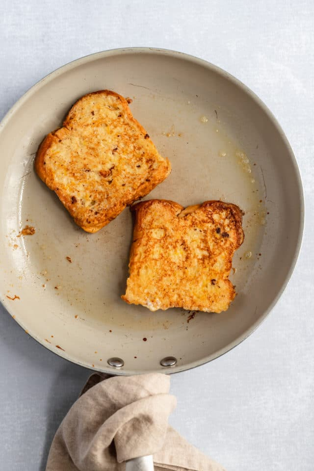 cooking two pieces of brioche French toast on a large skillet