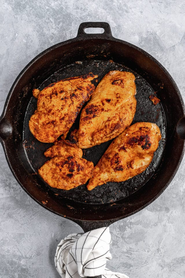 seasoned chicken cooking in a cast iron skillet