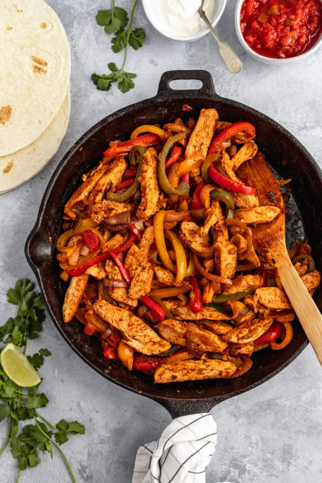 chicken and fajitas cooking in a cast iron skillet for chicken fajitas