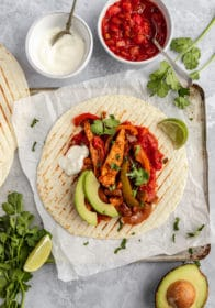 chicken fajita topped with avocado slices and sour cream