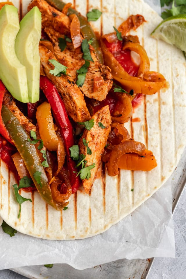 chicken fajitas served on flour tortillas with seasoned chicken, bell peppers and avocado slices