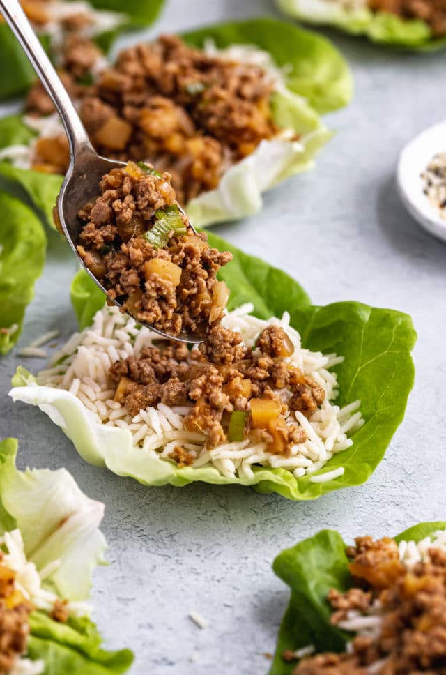 spooning ground chicken into lettuce wrap filled with rice