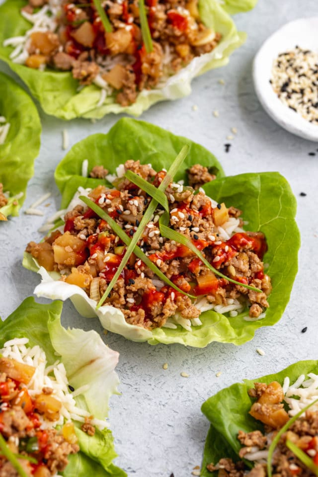 Asian chicken lettuce wraps topped with green onion and sriracha