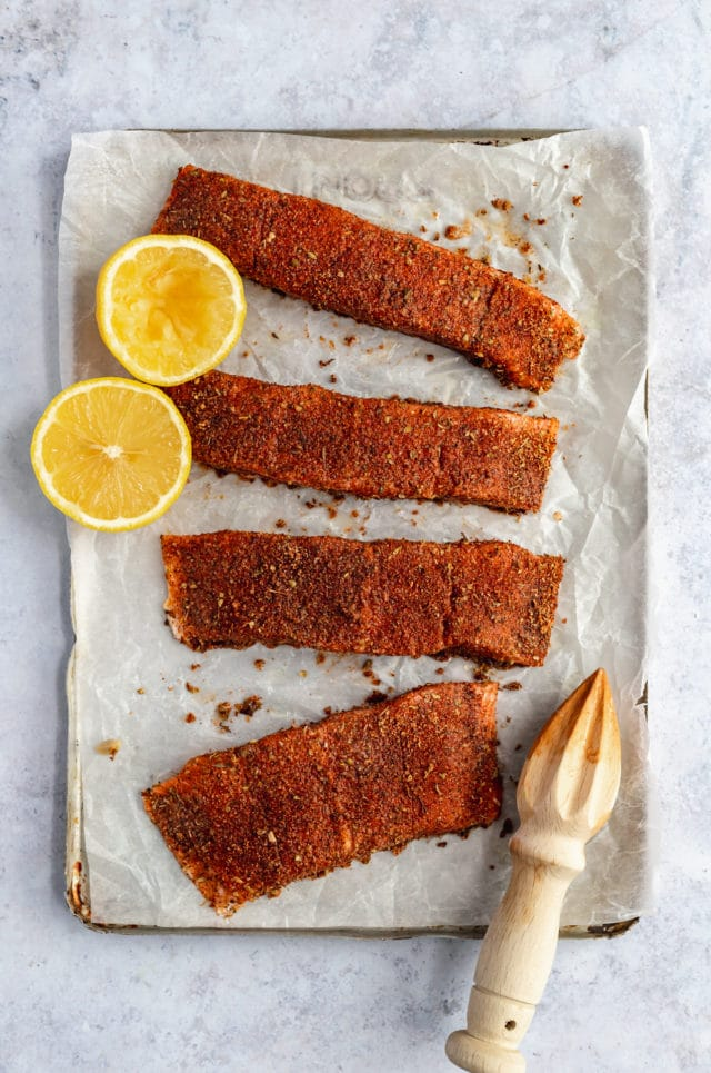 raw salmon on parchment paper with a rub