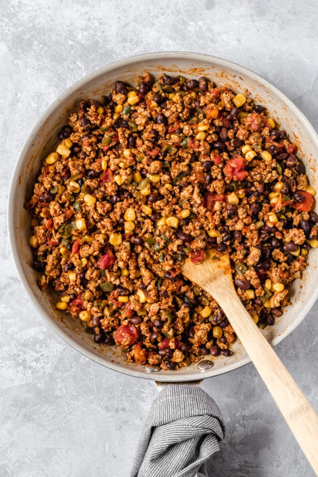 mixing ground turkey with other taco casserole ingredients in a large skillet