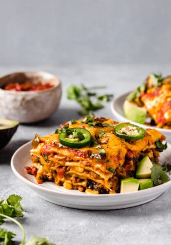 serving of taco casserole on a white plate served with salsa and diced avocado