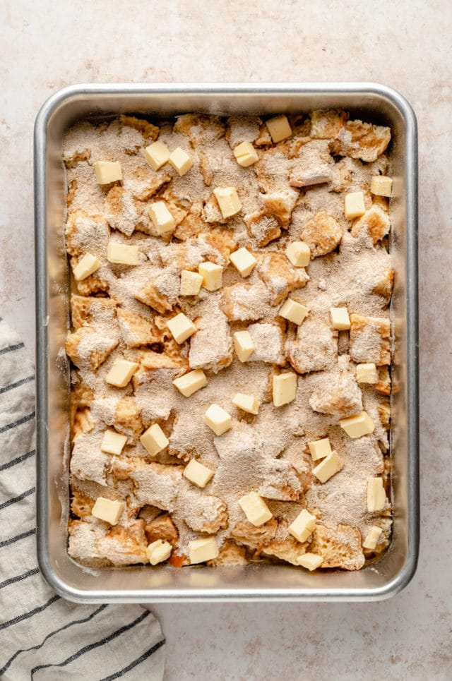 placing all of the layers for French toast casserole on a large baking sheet pan