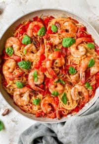 tomato based pasta cooked in a skillet with shrimp and topped with fresh basil