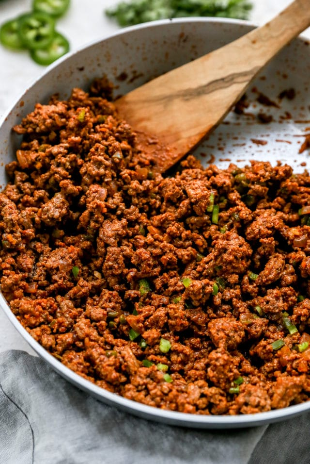 seasoned taco meat cooking in a large skillet