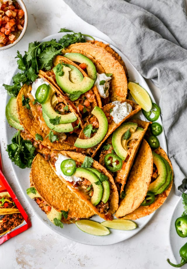 crispy beef tacos topped with avocado slices and sour cream