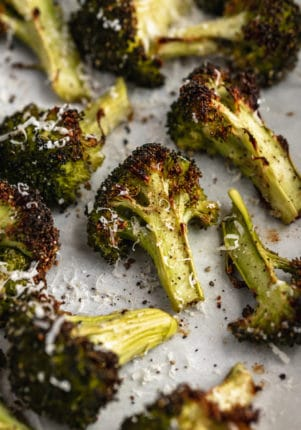 roasted broccoli on a baking sheet topped with parmesan cheese