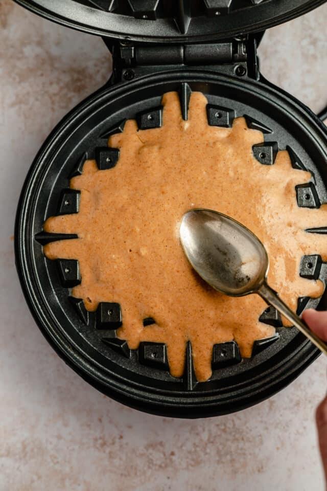 spoon pumpkin waffle batter over waffle iron