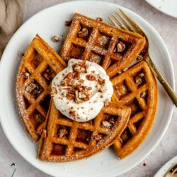 pumpkin waffles on a white plate served with yogurt, chopped pecans and syrup