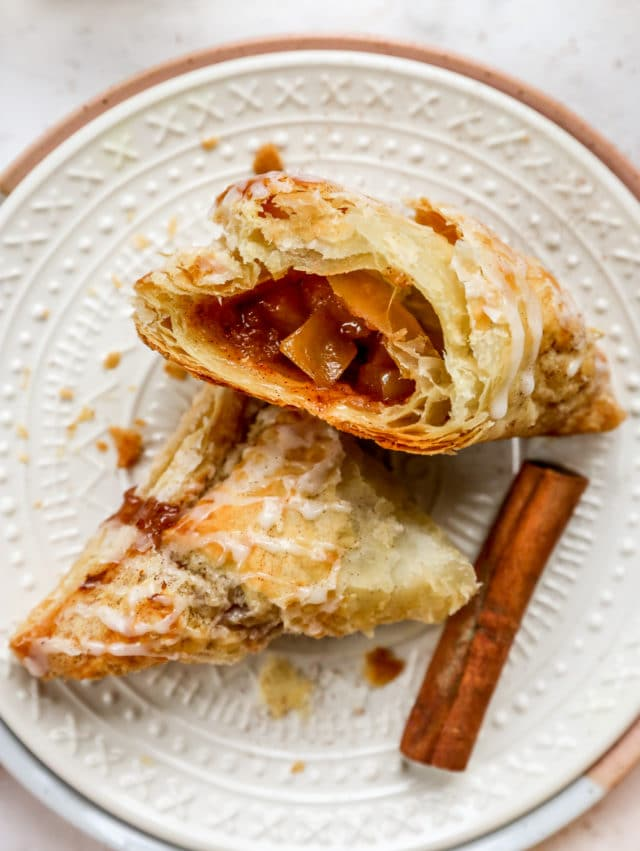apple turnovers served on a plate with a bite taken out of one