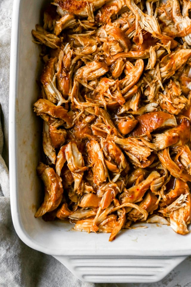crockpot BBQ chicken shredded in a white serving dish