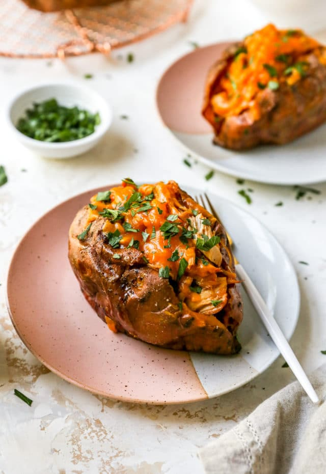 stuffed sweet potato on a plate served with a fork