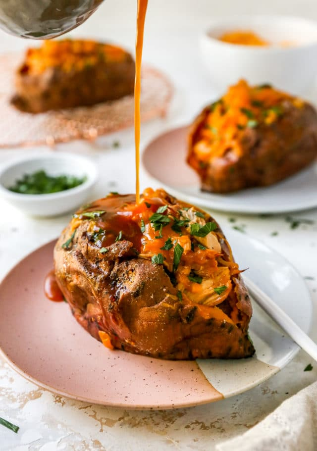drizzling barbecue sauce over stuffed sweet potato