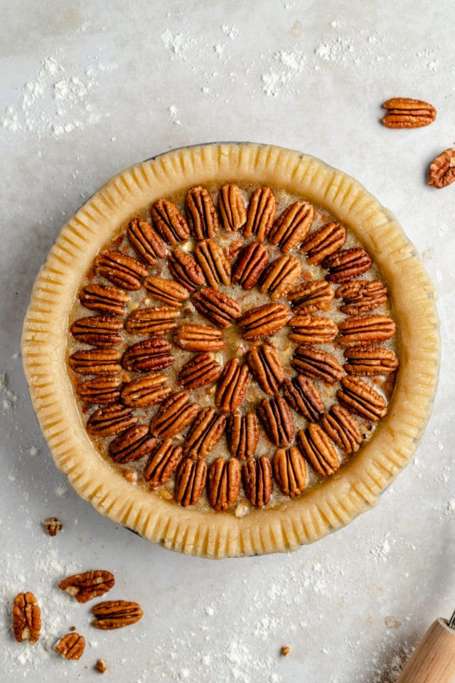 layering pecans on a pecan pie before baking