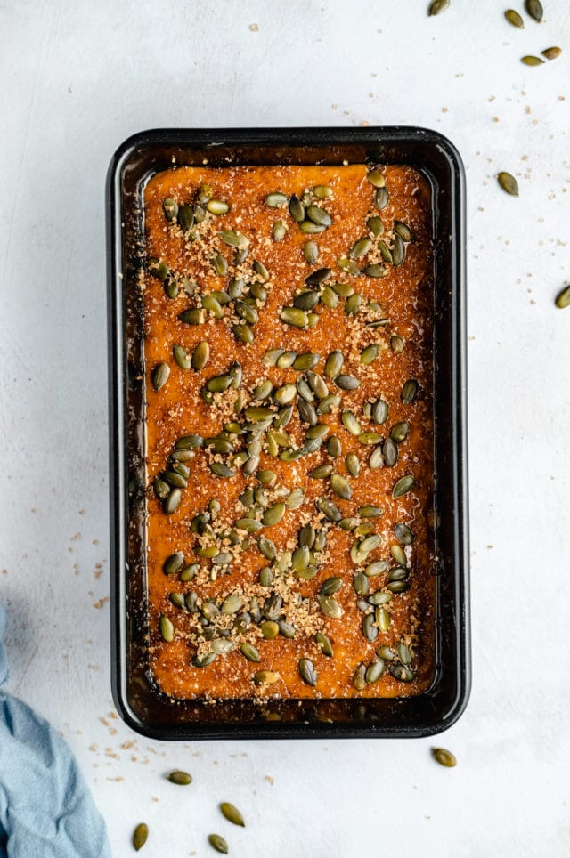 pumpkin bread in loaf pan and topped with pumpkin seeds