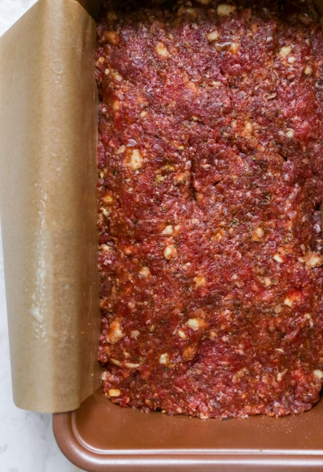 meatloaf mixture in a loaf pan lined with parchment paper