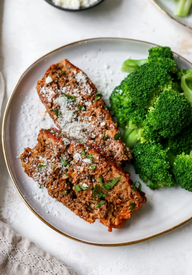 slices of meatloaf on a plate served with broccoli