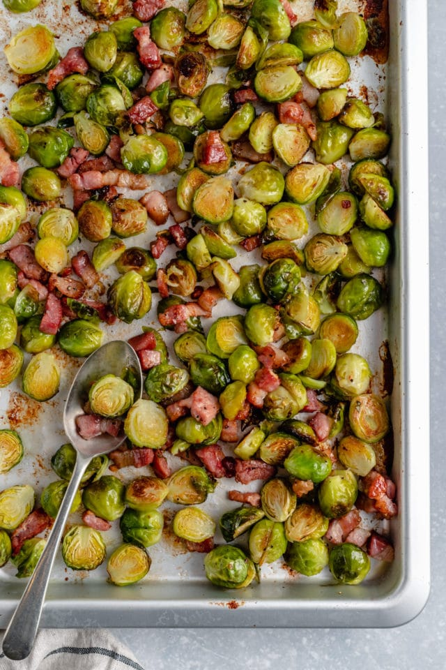 Brussels sprouts cooked with bacon on a large baking sheet pan