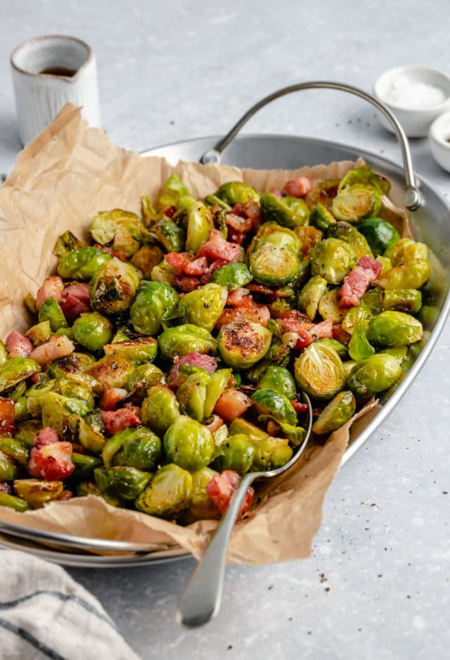 Roasted Brussels sprouts with bacon and maple syrup in a serving dish