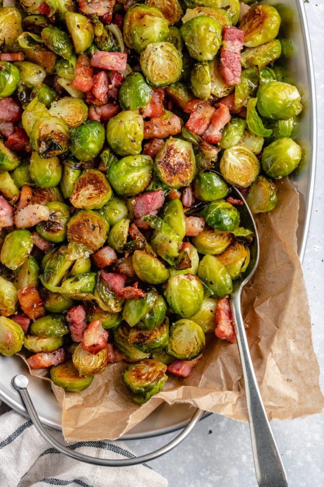 Bacon dishing out Roasted Brussels Sprouts with a large serving spoon