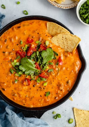 cheesy black eyed pea dip garnished with cilantro and tortilla chips