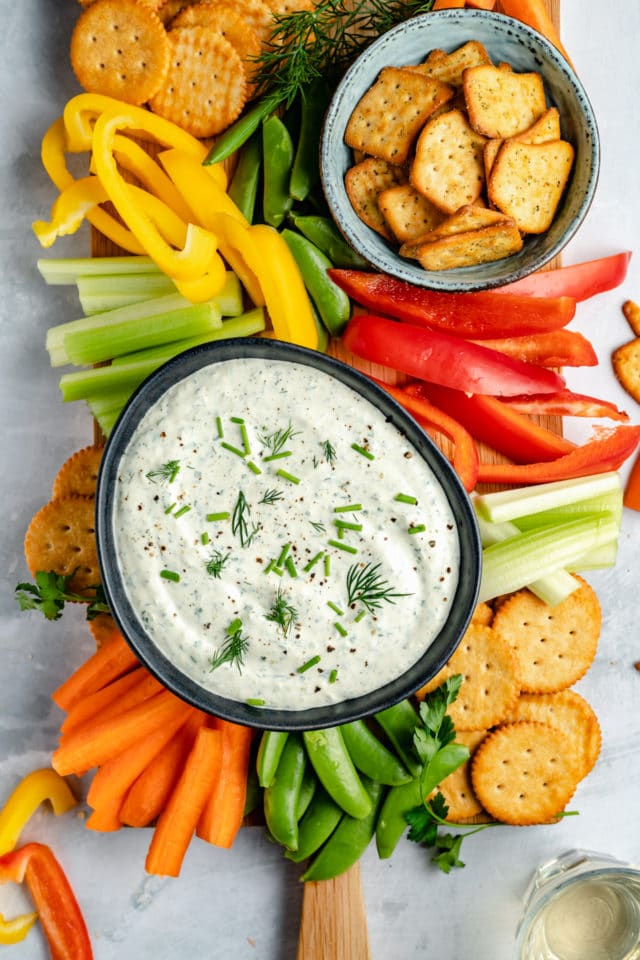 creamy herb dip served in a small bowl with raw veggies