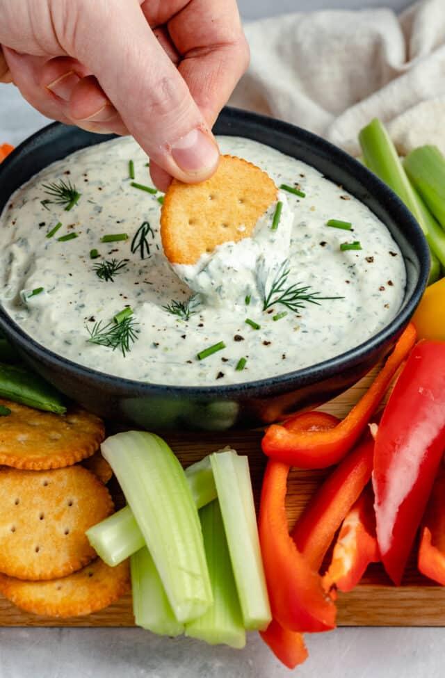 hand dipping Ritz cracker into creamy herb dip