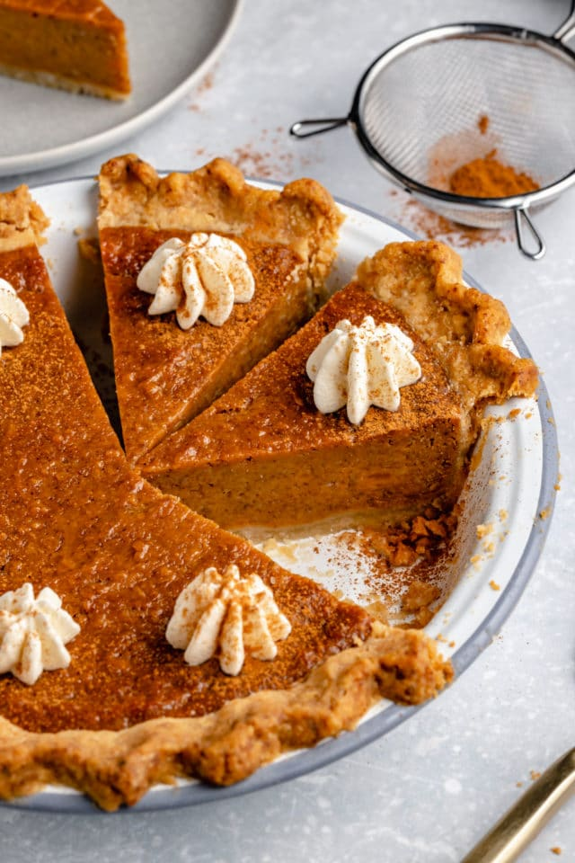 slices of sweet potato pie topped with whipped cream in a pie plate