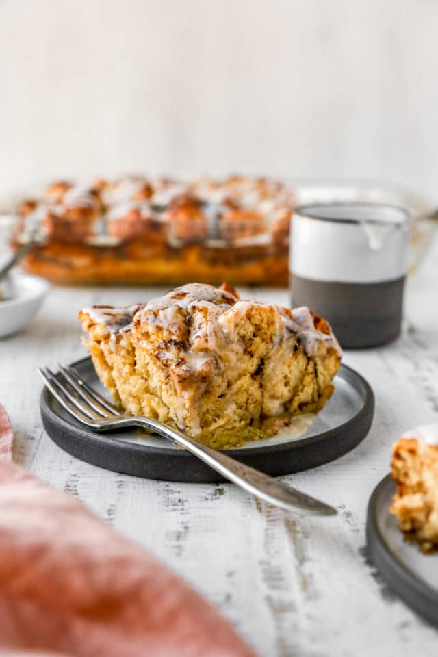 serving of cinnamon roll casserole on a plate with a fork