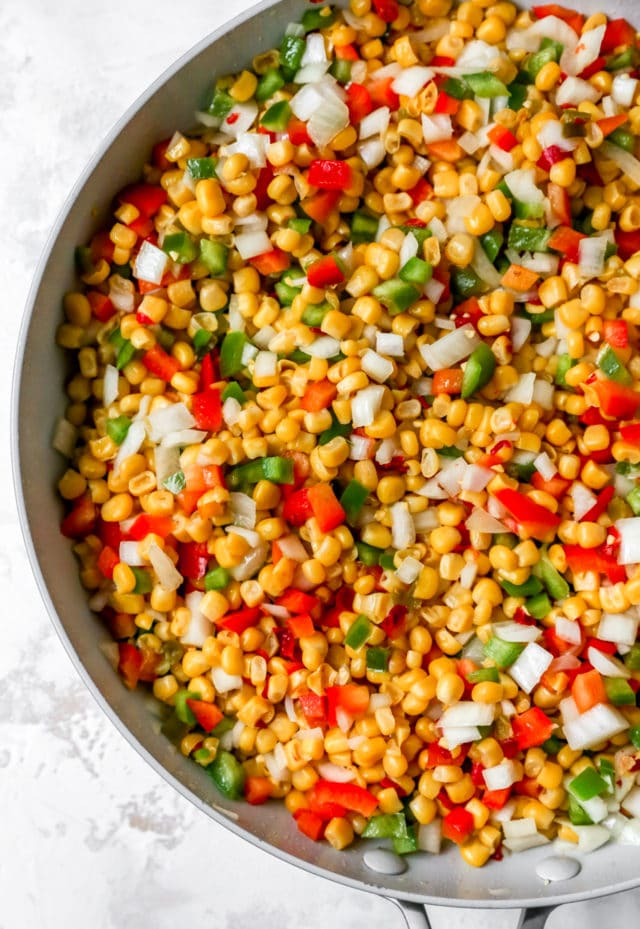sautéing corn and veggies in a large skillet