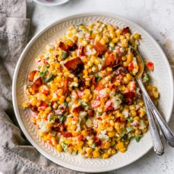 creamed corn with a bacon topping served in a large white shallow bowl