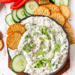 spinach dip in a bowl with crackers and cucumbers dipped in
